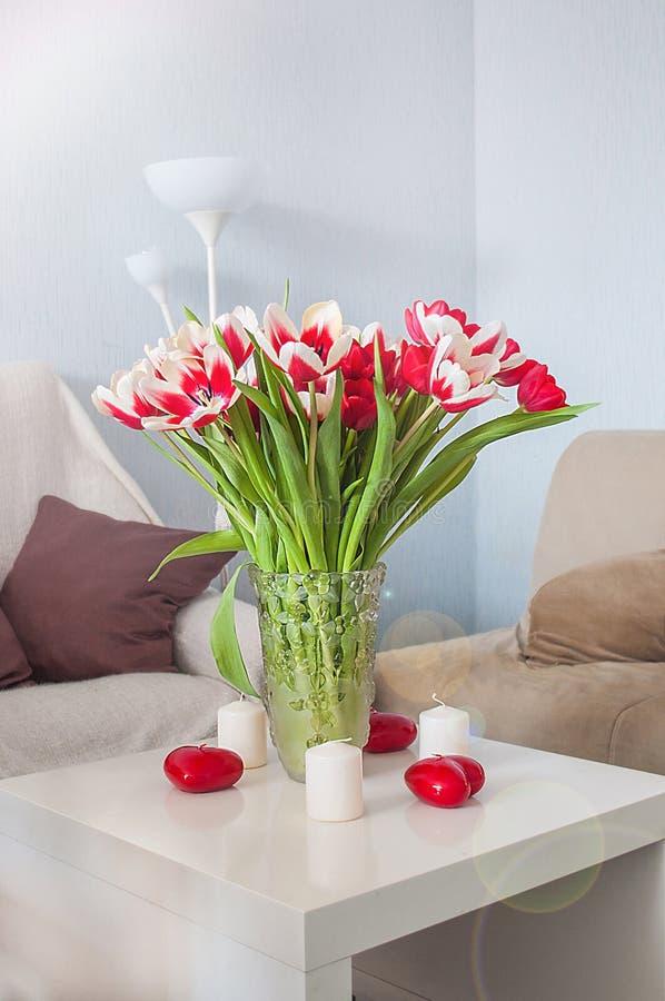 En bukett av röda och vita tulpan i en glass vas på en vit tabell royaltyfri fotografi