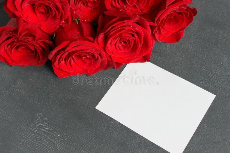 En bukett av röda rosor och ett ark av vitbok för att skriva, som skriver texten på en träsvart bakgrund arkivbild