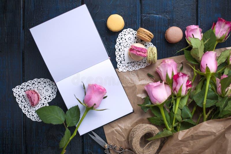 En bukett av rosor är rosa, i grå färgpapper och en vit hjärta Steg på en öppen anteckningsbok Söta pastamakron av olika färger, royaltyfri bild