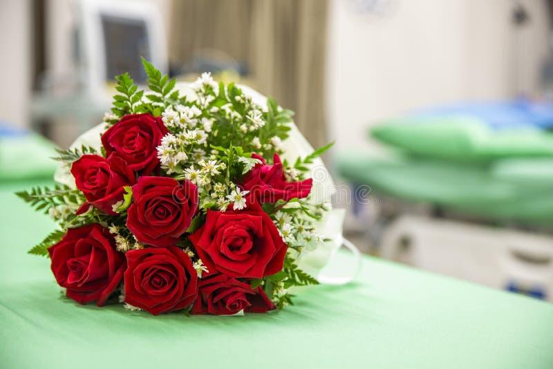 en bukett av rosor på en sjukhussäng royaltyfri bild