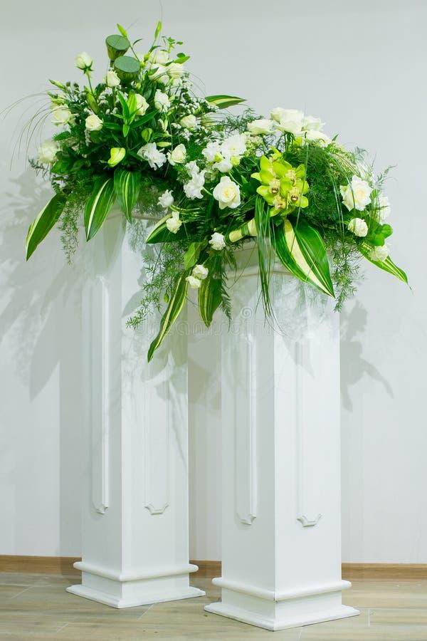En bukett av vita rosor, gula påskliljor, grönska och lotusblommaställningar i en vas på en marmor står arkivfoto