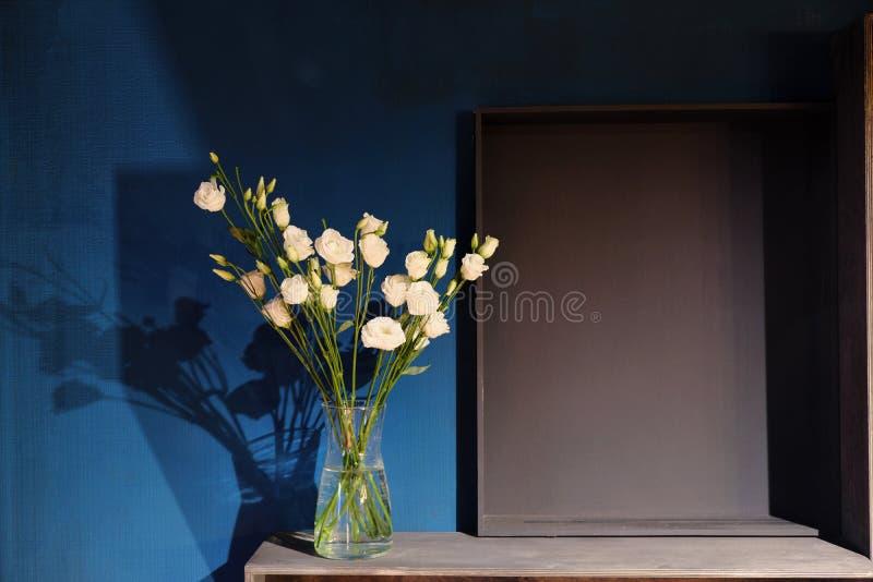En bukett av vita rosor i en exponeringsglasvas står mot ett mörkt - den blåa väggen shelves trä arkivfoto
