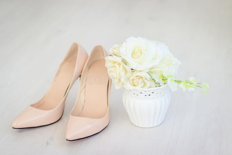 En bukett av vita rosor i en vas och skor Bröllopsklänning och skor royaltyfria bilder