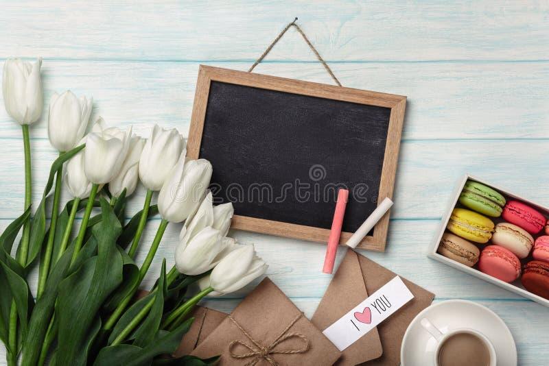 En bukett av vita tulpan med kritabrädet, koppen kaffe, förälskelseanmärkningen och macarons på blåa träbräden royaltyfri fotografi