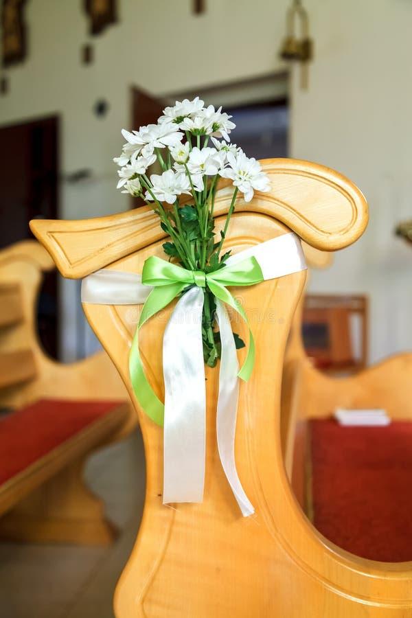 En bukett av vita tusenskönor binds till baksidan av en stol royaltyfri foto