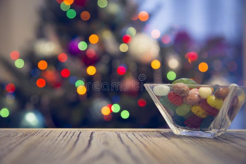 En bunke av godisar på en trätabell mot den dekorerade julgranen arkivbild