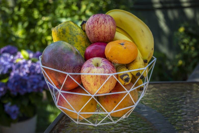 En bunke av läcker ny frukt med äpplen, bananer, apelsiner, mango och papayas arkivfoto