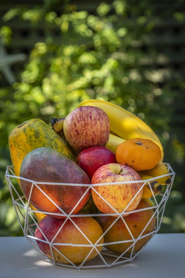 En bunke av läcker ny frukt med äpplen, bananer, apelsiner, mango och papayas arkivbilder