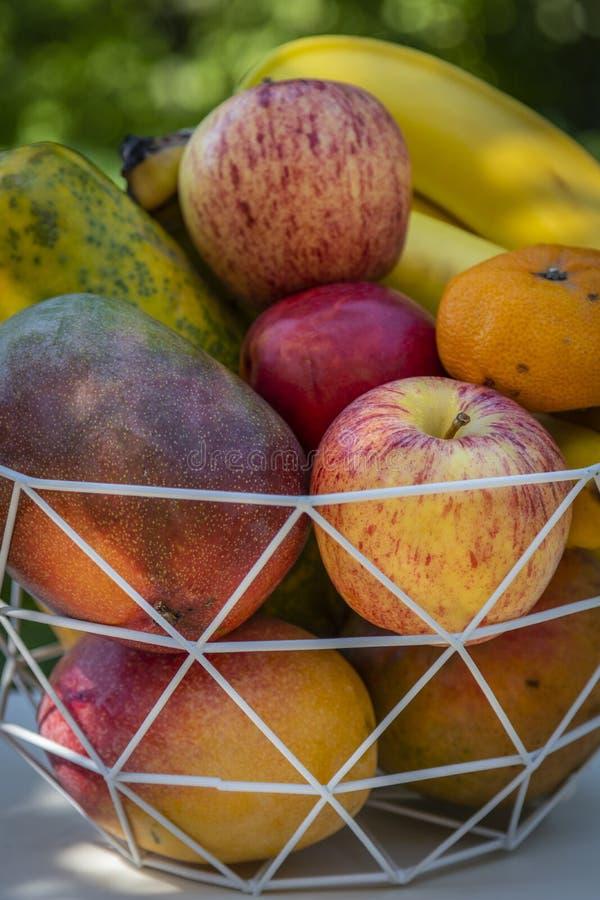 En bunke av läcker ny frukt med äpplen, bananer, apelsiner, mango och papayas arkivfoton