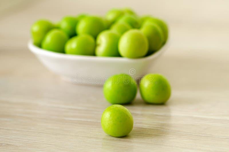 En bunke av nya gröna plommoner på tabellen royaltyfria foton