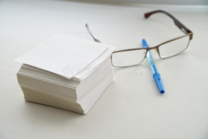 En bunt av ark för rekord, exponeringsglas och en reservoarpenna är på en vit tabell vid fönstret i kontoret Arbete på att katalo arkivbild