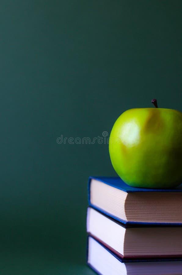 En bunt av böcker med ett grönt äpple på dem arkivbilder
