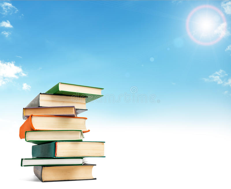 En bunt av böcker på det vita golvet mot blå himmel arkivbilder