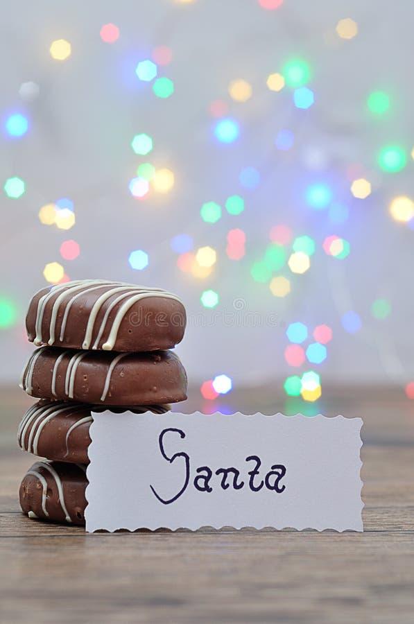 En bunt av choklad täckte kex med en anmärkning för jultomten royaltyfri bild