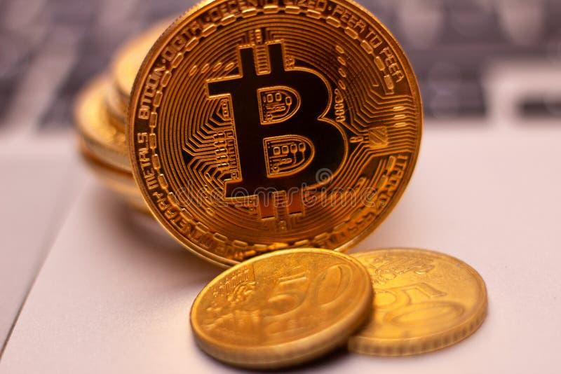 En bunt av det guld- bitcoinmyntet på ett silvertangentbord av bärbara datorn Faktiskt cryptocurrencybegrepp Bryta av bitcoins di arkivfoto