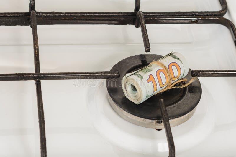 En bunt av hundra-dollar r?kningar p? en gasugn i mitten av gaskomfort, gasen br?nner inte arkivbild