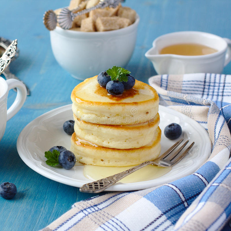 En bunt av kväv pannkakor med med honung och blåbär på en frukosttabell arkivbilder