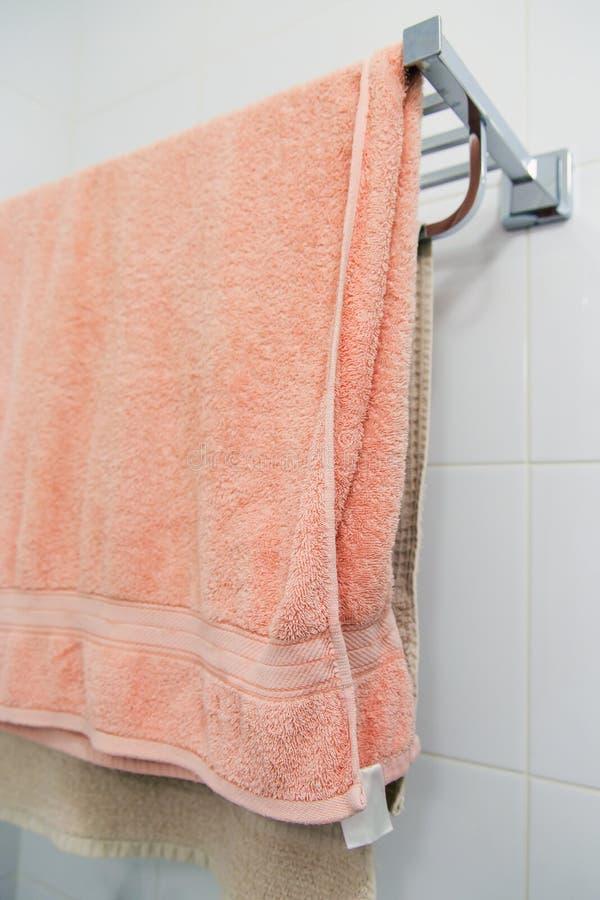 En bunt av mång--färgade handdukar på en metallhylla royaltyfria foton