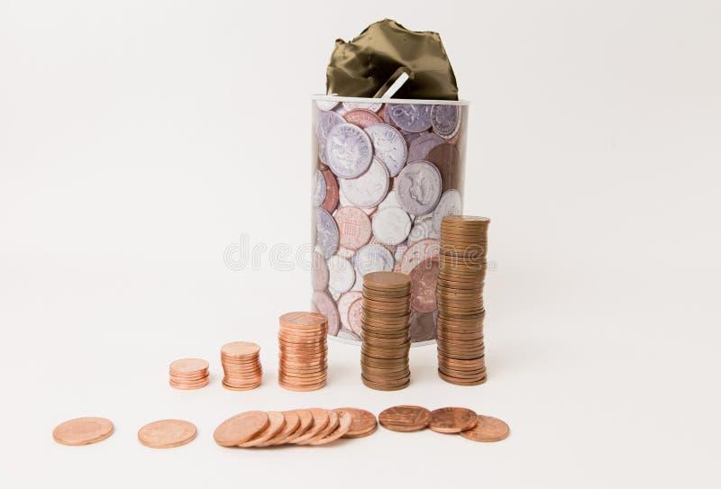 En bunt av mynt som står en framdel av den öppnade metallsparbössan arkivfoto