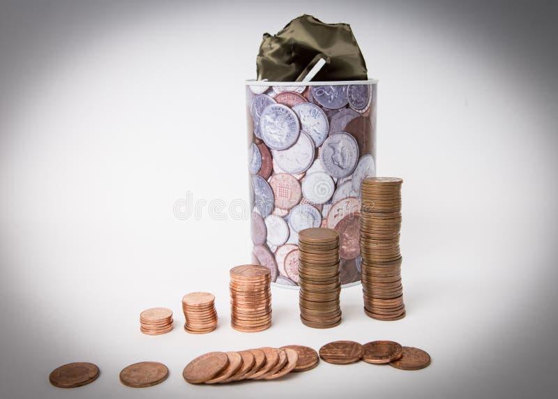En bunt av mynt som står en isolerad framdel av metallsparbössan Finans arkivbild