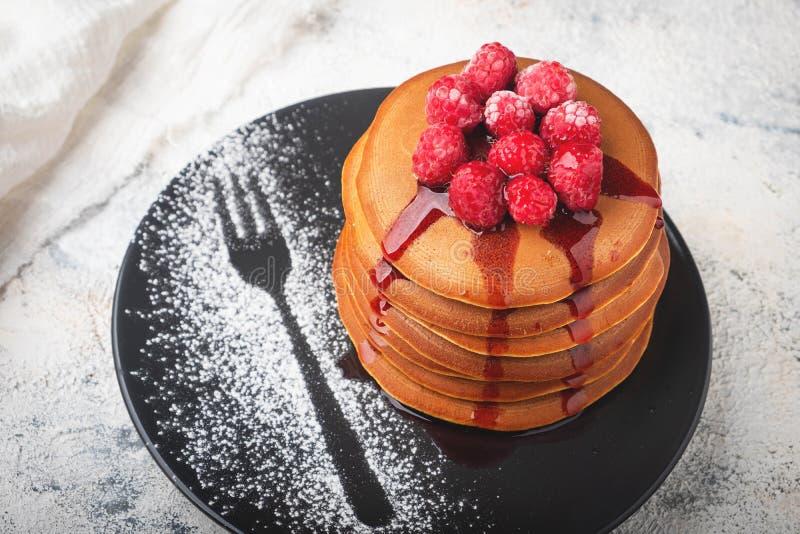 En bunt av pannkakor på en platta med hallon och bärsås royaltyfri fotografi