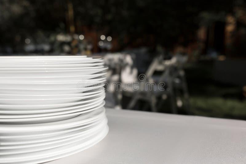 En bunt av rena vita plattaställningar på en tabell med en vit bordduk i den öppna luften Buffé på partiet arkivbild