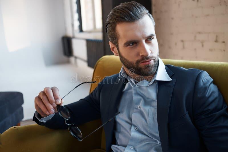En busca de la inspiración El hombre de negocios hermoso pensativo está sosteniendo los vidrios y está pensando en futuro fotos de archivo libres de regalías