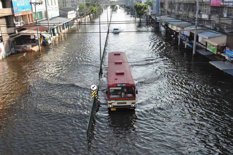 En buss håller det tjänste- för att öppna i en översvämmad gata av Bangkok, Thailand, på 06 November 2011 royaltyfria foton