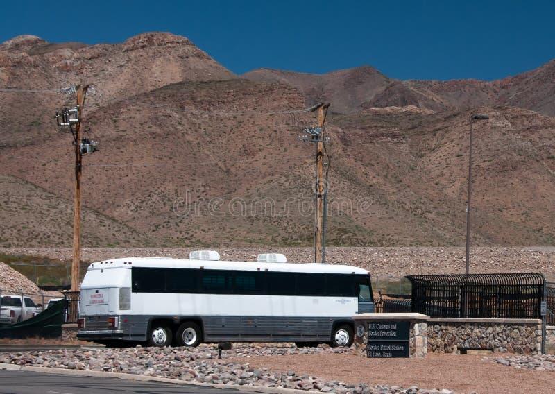 En buss som bär invandrare, ankommer på USA-gränsbevakningstationen, El Paso Texas, tillfälligt hus/bearbetaområde arkivbild