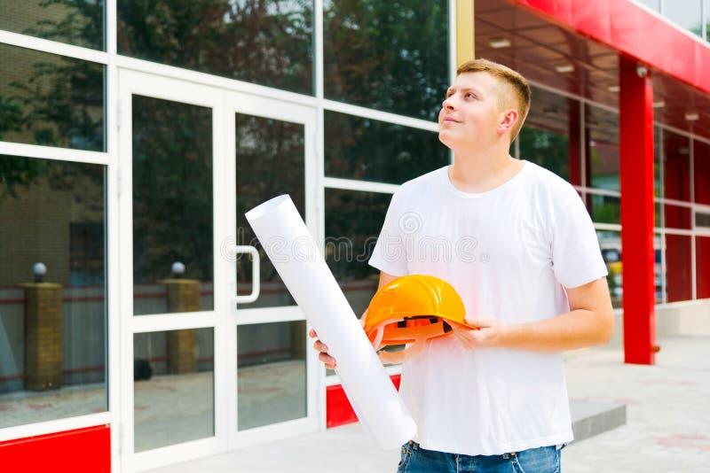 En byggmästare som ser en byggnad med ett leende Nöjet av prodelanoy arbete Tekniker på en konstruktionsplats med planet av arkivbilder