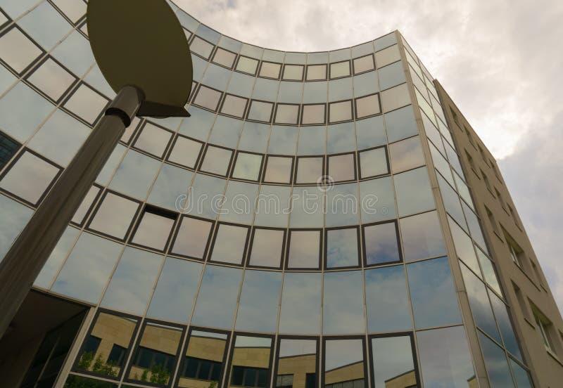 En byggnad reflekterar den molniga himlen arkivfoto