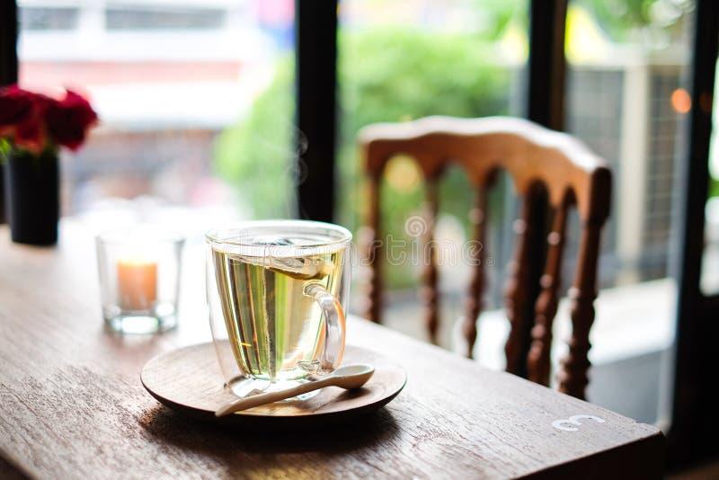 En cafetería, el té caliente de la lavanda en el servicio de cristal con la cuchara de madera y el platillo en la tabla con la si fotografía de archivo