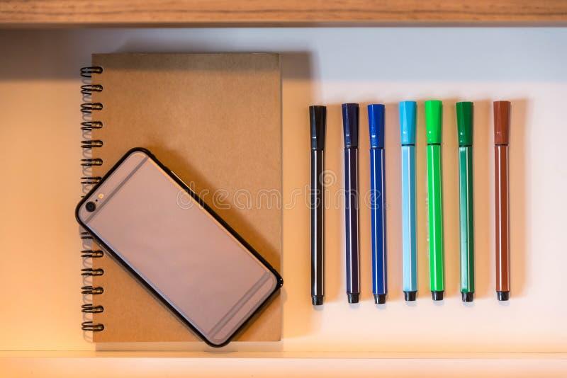 En cajón tiene plumas del color, bosqueja el libro y el teléfono celular imágenes de archivo libres de regalías
