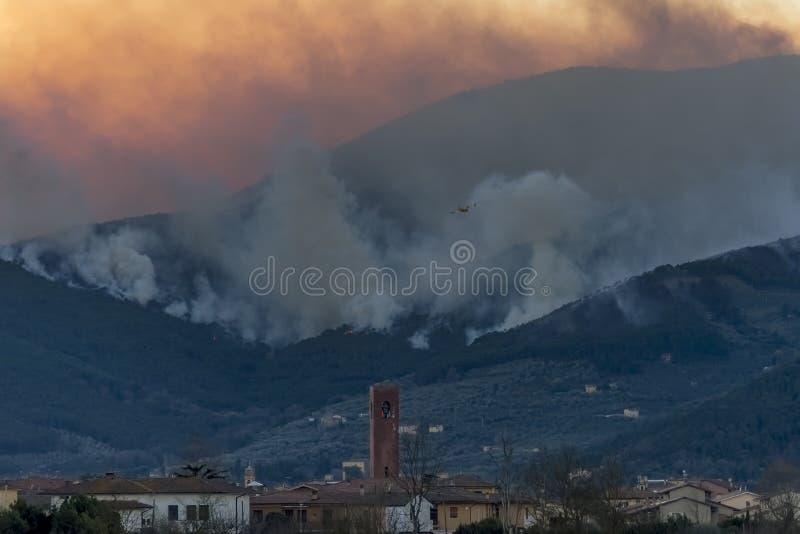 En canadair flyger över mitten av Bientina, medan försöka att släcka en vidsträckt brand på monteringen Pisano, Tuscany, Italien arkivfoto