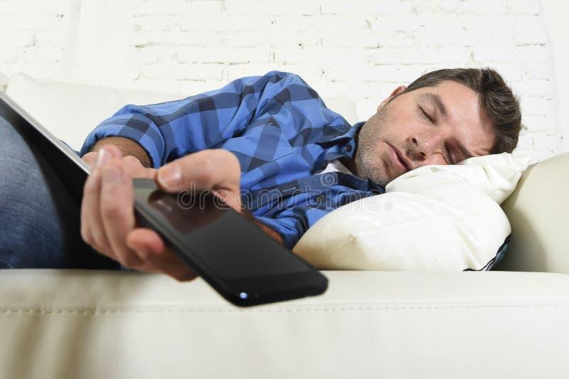 En casa sofá dormido que cae cansado y con exceso de trabajo atractivo joven con el teléfono móvil y el cojín digital de la table imagenes de archivo