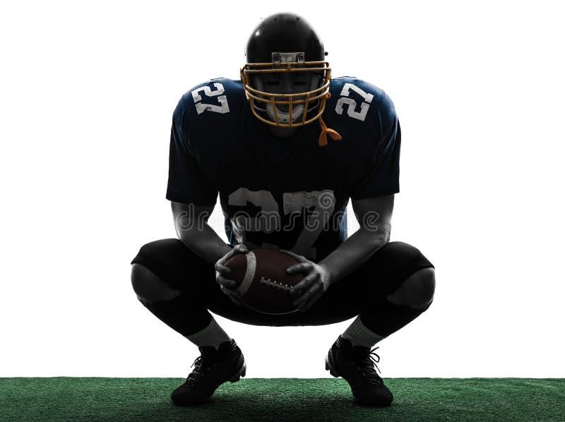 Huka sig ned silhouette för amerikanfotbollsspelareman fotografering för bildbyråer