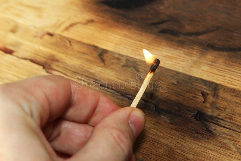 En Caucasian hand som rymmer en tänd match Denna bild innehåller en träbakgrund och kan också vara van vid föreställer brandstart royaltyfria foton