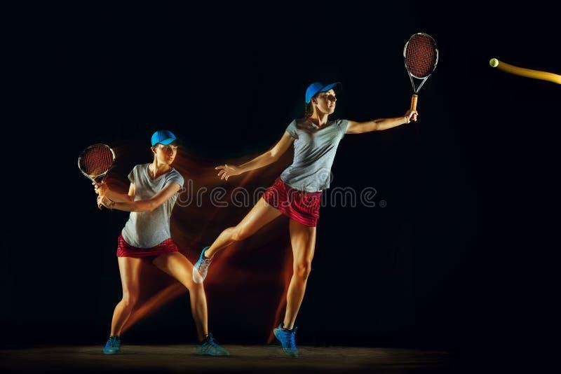 En caucasian kvinna som spelar tennis på svart bakgrund i blandat ljus royaltyfria foton