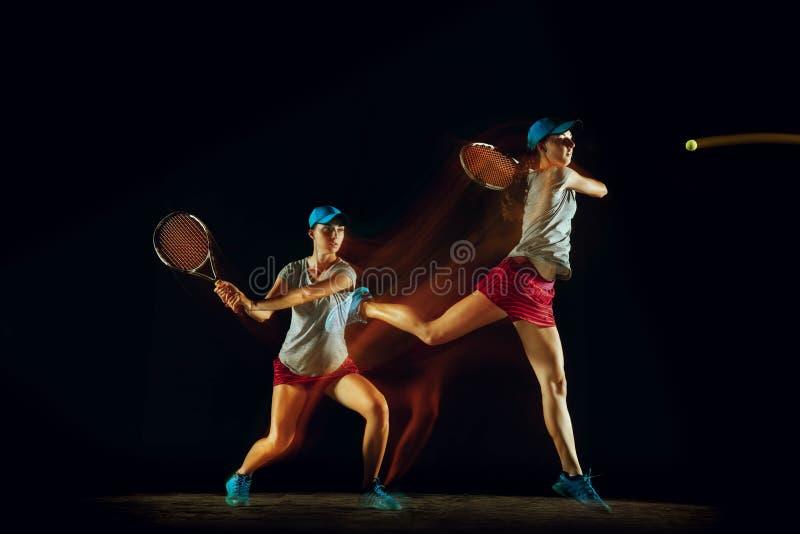 En caucasian kvinna som spelar tennis på svart bakgrund i blandat ljus royaltyfri fotografi