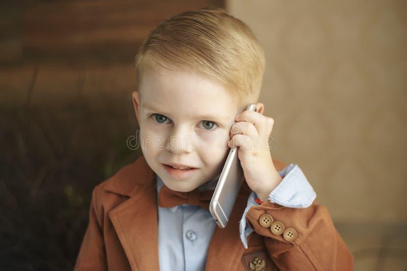 En Caucasian pojke som kallar att le bakgrundsstudioståenden royaltyfri bild