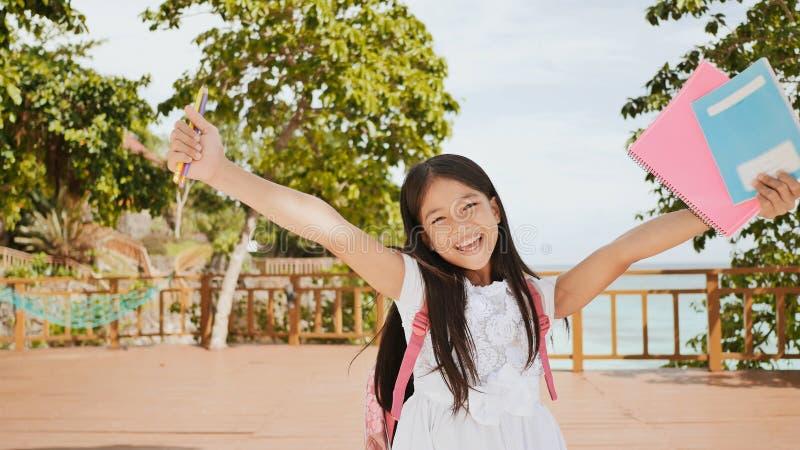 En charmig filippinsk skolflicka med en ryggsäck och böcker i en parkera av flickan för kust A poserar joyfully och att lyfta hen royaltyfri fotografi