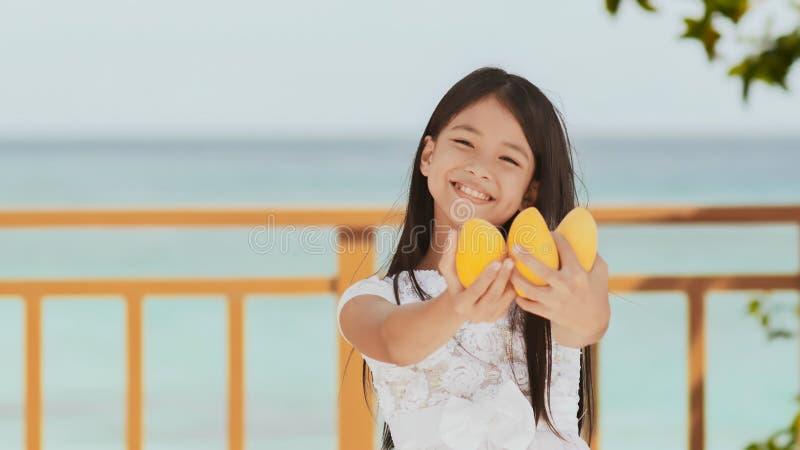 En charmig filippinsk skolflickaflicka i en vit klänning och ett långt hår poserar positivt med en mango i henne händer Baikal la royaltyfria foton