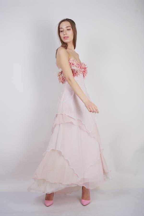En charmig ung caucasian flicka står i en rosa lång studentbalklänning med blommakronblad på hennes bröstkorg och poserar p arkivfoto