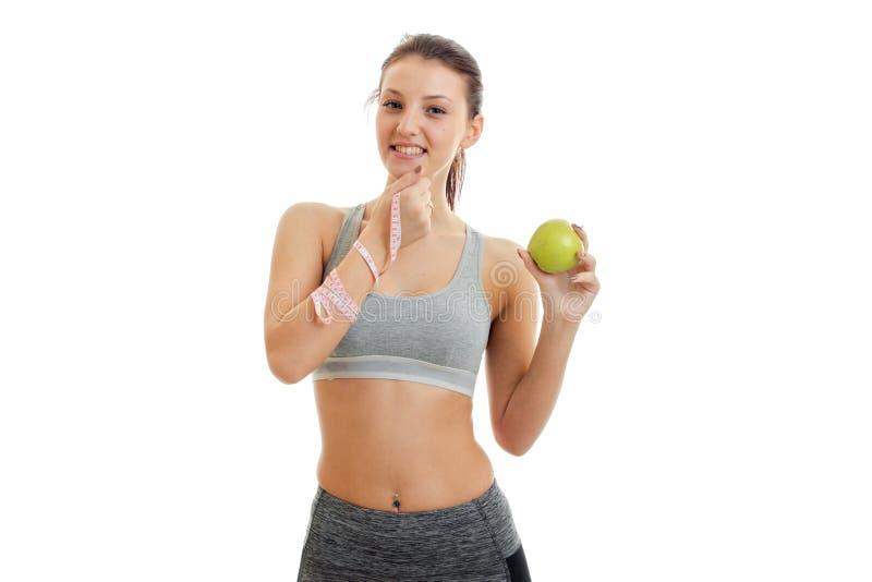 En charmig ung flicka äter en grönt Apple och le arkivfoto