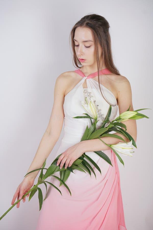 En charmig ung flicka med stora ögon och bruna hårställningar utan makeup i en modeklänning på en vit bakgrund i studion B royaltyfri fotografi