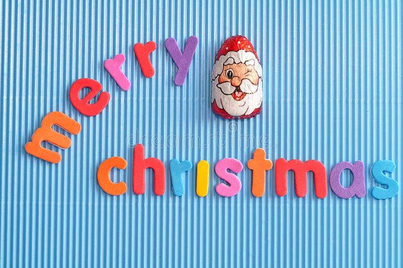 En choklad som täckas med Santa Clau, vänder mot omslaget med den glade julen för ord royaltyfri foto