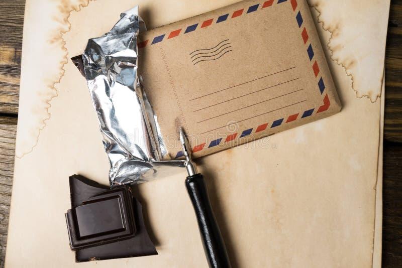En chokladstång och en reservoarpenna ligger på tappningpapper, en gammal trätabell Åtlöje upp royaltyfri foto
