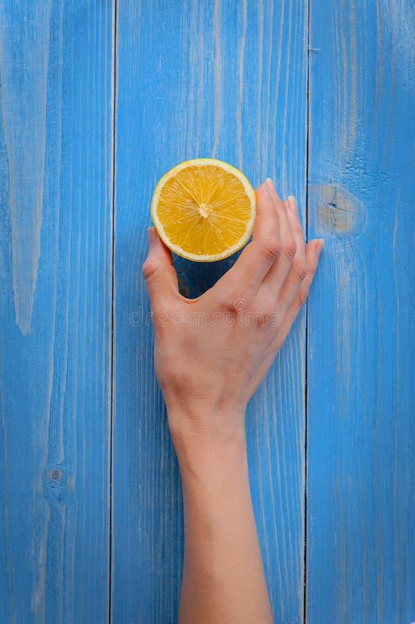 En citron för kvinnlig hand färgar den hållande halvan på en bakgrund av en trätabell som målas i blått arkivfoton