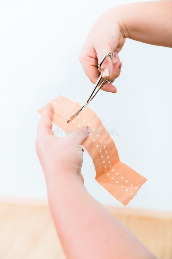 En clase de los primeros auxilios, el cortar del remiendo para lesiones más pequeñas fotografía de archivo