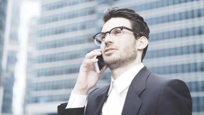 En closeup av en allvarlig affärsman som har en appell på telefonen arkivbild